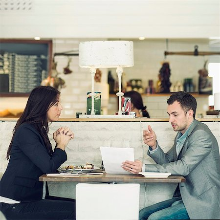 Side view of businessman with female colleague discussing at restaurant table Stock Photo - Premium Royalty-Free, Code: 698-07611883