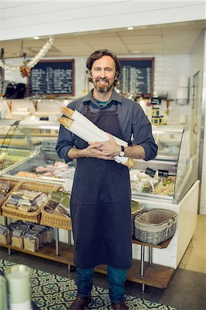 Portrait of mature male baker holding loaves of bread in supermarket Stock Photo - Premium Royalty-Free, Code: 698-07611899