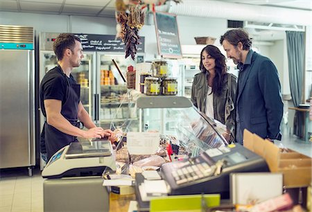 Salesman attending couple in supermarket Stock Photo - Premium Royalty-Free, Code: 698-07611904