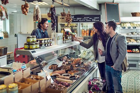 shop - Salesman attending couple at display counter in supermarket Stock Photo - Premium Royalty-Free, Code: 698-07611902
