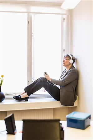 Full length of businesswoman listening music while sitting on window sill Stock Photo - Premium Royalty-Free, Code: 698-07611942