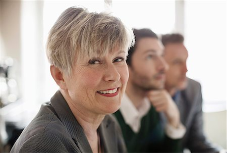 Portrait of happy businesswoman with colleagues in background at office Stock Photo - Premium Royalty-Free, Code: 698-07611954