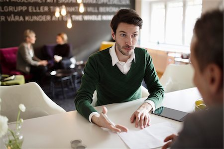 sold sign - Serious businessman discussing with colleague at office desk Stock Photo - Premium Royalty-Free, Code: 698-07611958