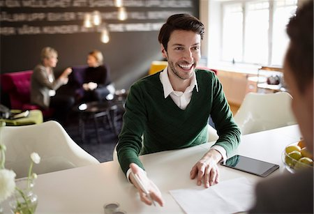 sold sign - Happy businessman discussing with colleague at office desk Stock Photo - Premium Royalty-Free, Code: 698-07611959