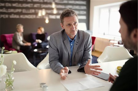 Businessman gesturing while discussing with male colleague at desk Stock Photo - Premium Royalty-Free, Code: 698-07611960