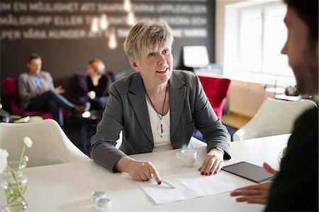 Senior businesswoman discussing with male colleague at office desk Stock Photo - Premium Royalty-Free, Code: 698-07611961