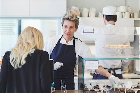 sweets - Female cafe worker attending customer at counter Stock Photo - Premium Royalty-Free, Code: 698-07611975