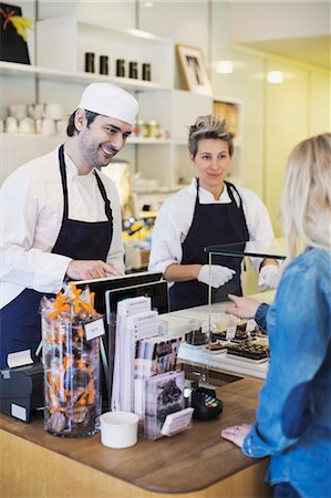 sweets - Cafe worker attending female customer at counter Stock Photo - Premium Royalty-Free, Code: 698-07611976