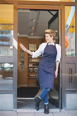 retail store - Full length of happy female owner gesturing while standing at cafe entrance Stock Photo - Premium Royalty-Free, Code: 698-07611979