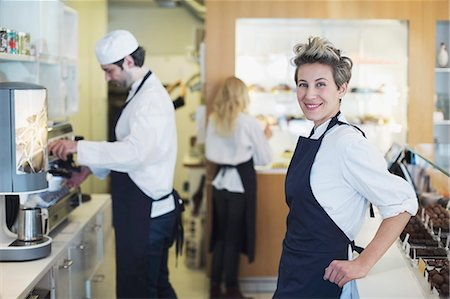 Portrait of smiling female cafe owner with colleagues working in background Stock Photo - Premium Royalty-Free, Code: 698-07611971
