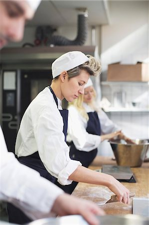 sweets - Side view of female baker baking with colleagues in commercial kitchen Stock Photo - Premium Royalty-Free, Code: 698-07611985