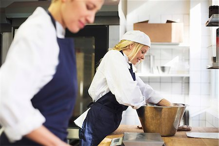 Young female baker working with colleague in commercial kitchen Stock Photo - Premium Royalty-Free, Code: 698-07611989