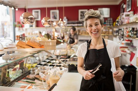 Portrait of happy saleswoman cutting cheese at counter in supermarket Stock Photo - Premium Royalty-Free, Code: 698-07611996