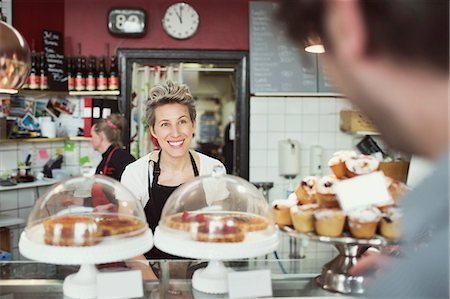 Smiling saleswoman attending customer in supermarket Stock Photo - Premium Royalty-Free, Code: 698-07612000