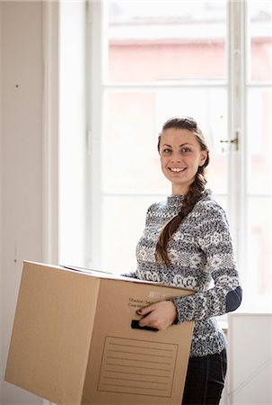 Portrait of happy young woman carrying moving box in new home Stock Photo - Premium Royalty-Free, Code: 698-07635196