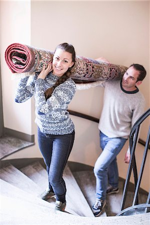 Portrait of young woman with man carrying rolled carpet up stairs Stock Photo - Premium Royalty-Free, Code: 698-07635197
