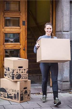 Full length portrait of young woman with cardboard box walking on sidewalk Stock Photo - Premium Royalty-Free, Code: 698-07635198