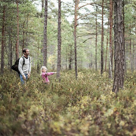 Girl showing something to father in forest Stock Photo - Premium Royalty-Free, Code: 698-07635206