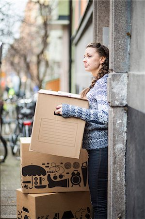 renting - Young woman with moving boxes outdoors Stock Photo - Premium Royalty-Free, Code: 698-07635202