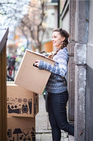 Side view of young woman carrying cardboard box outdoors Stock Photo - Premium Royalty-Free, Code: 698-07635203
