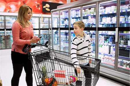 Mother and son with shopping cart in grocery store Stock Photo - Premium Royalty-Free, Code: 698-07635224