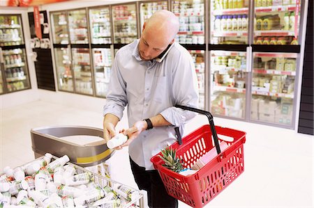 purchase - Mid adult man answering mobile phone while shopping in supermarket Stock Photo - Premium Royalty-Free, Code: 698-07635225