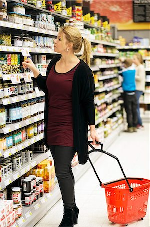 Mid adult woman shopping groceries with children in background at supermarket Stock Photo - Premium Royalty-Free, Code: 698-07635229