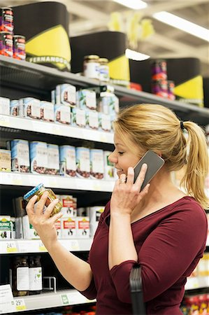 Mid adult woman answering smart phone while buying groceries in supermarket Stock Photo - Premium Royalty-Free, Code: 698-07635234