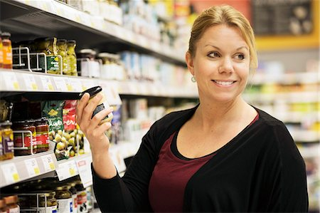 Smiling woman looking away while buying groceries in supermarket Stock Photo - Premium Royalty-Free, Code: 698-07635230