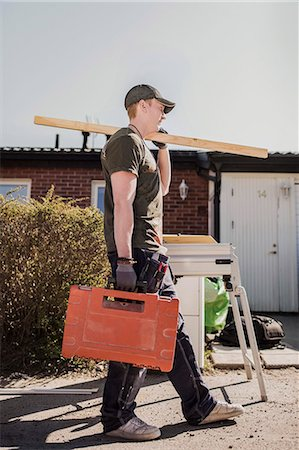 Full length side view carpenter with wooden plank and toolbox walking at site Stock Photo - Premium Royalty-Free, Code: 698-07635268