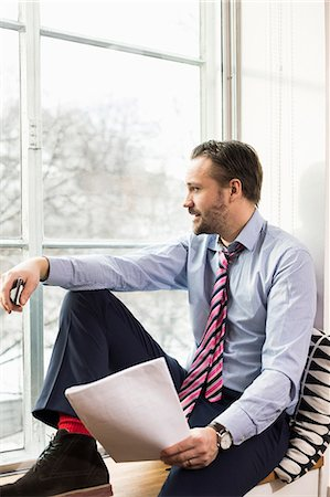 Mid adult businessman looking through window while sitting on ledge Stock Photo - Premium Royalty-Free, Code: 698-07635277