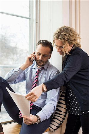 partnership - Businessman answering smart phone while discussing over document with female colleague by office window Stock Photo - Premium Royalty-Free, Code: 698-07635279