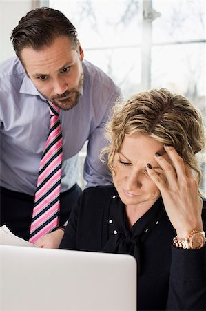 Senior businesspeople looking at laptop in office Stock Photo - Premium Royalty-Free, Code: 698-07635280