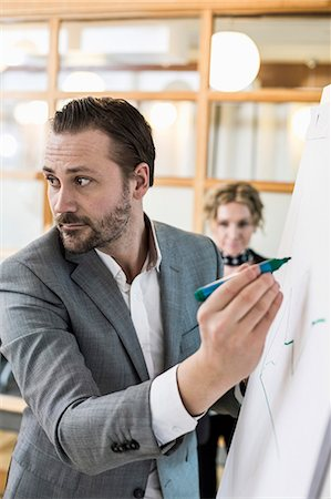 Mid adult businessman writing on flip chart with female colleague in background at office Stock Photo - Premium Royalty-Free, Code: 698-07635292
