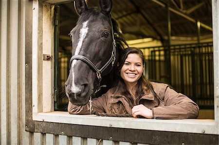 Portrait of happy young woman with horse in stable Stock Photo - Premium Royalty-Free, Code: 698-07635306