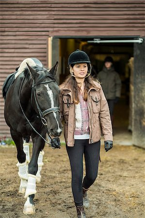 Young woman with horse walking outside barn with man in background Stock Photo - Premium Royalty-Free, Code: 698-07635318