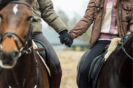 Low section of couple holding hands while riding horses Stock Photo - Premium Royalty-Free, Code: 698-07635322
