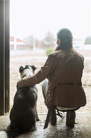 Full length rear view of young woman arm around dog in doorway of horse stable Stock Photo - Premium Royalty-Free, Code: 698-07635334