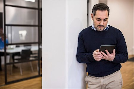 Mid adult businessman using digital tablet while leaning on column in office Stock Photo - Premium Royalty-Free, Code: 698-07635337