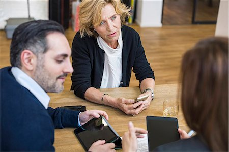 Businesspeople with digital tablets discussing at desk in office Stock Photo - Premium Royalty-Free, Code: 698-07635344