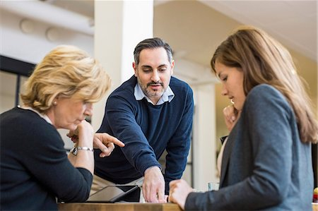 Businessman planning strategy with female colleagues at desk in office meeting Stock Photo - Premium Royalty-Free, Code: 698-07635346