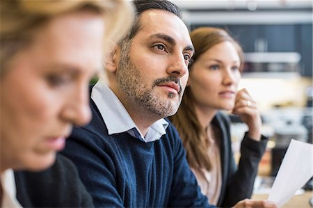 Concentrated businessman looking away in office meeting Stock Photo - Premium Royalty-Free, Code: 698-07635349