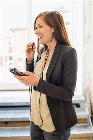 Smiling businesswoman listening to music through mobile phone in office Stock Photo - Premium Royalty-Free, Code: 698-07635340