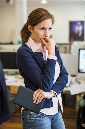 Thoughtful businesswoman holding digital tablet in office Stock Photo - Premium Royalty-Free, Code: 698-07635358