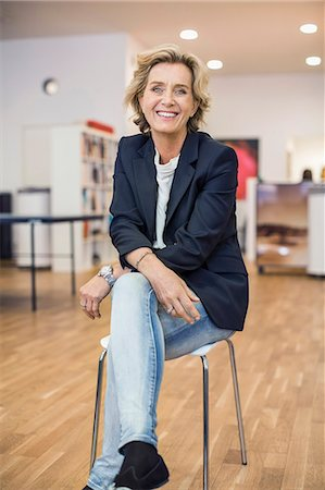 short hair - Full length portrait smiling businesswoman sitting on chair in office Stock Photo - Premium Royalty-Free, Code: 698-07635364