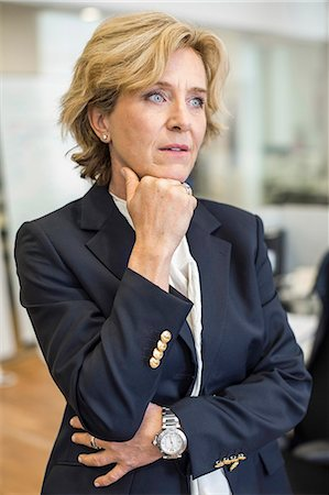 short hair - Thoughtful businesswoman with hand on chin in office Stock Photo - Premium Royalty-Free, Code: 698-07635365