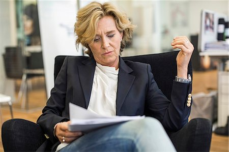 short hair - Mature businesswoman reading documents while sitting on chair in office Stock Photo - Premium Royalty-Free, Code: 698-07635366