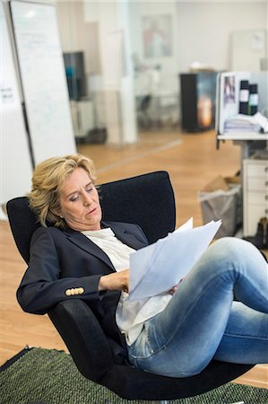 short hair - Relaxed businesswoman reading documents while sitting on chair in office Stock Photo - Premium Royalty-Free, Code: 698-07635367