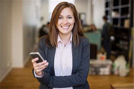 portrait smile caucasian one - Portrait of smiling businesswoman holding mobile phone in office Stock Photo - Premium Royalty-Free, Code: 698-07635378