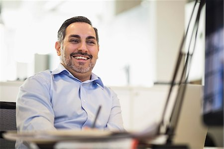 Happy businessman looking away in office Stock Photo - Premium Royalty-Free, Code: 698-07635381